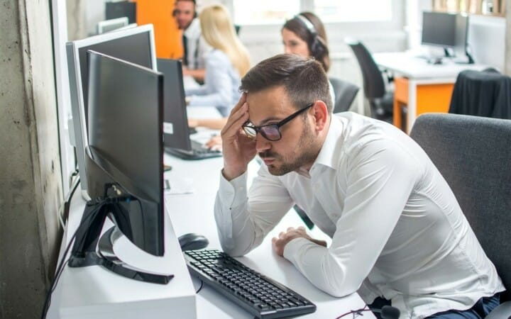 worker looking very frustrated at desk with computer